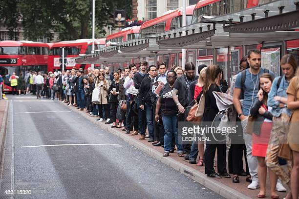 Commuters queue for buses as a 24 hour tube strike hits the morning rush hour at Victoria station central London on August 6 2015 The strike began at...