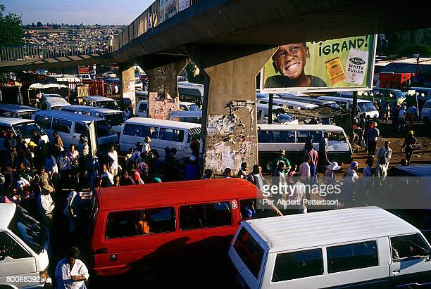 Commuters queue for mini bus taxis at Baragwanath taxi station on March 14 2005 in Soweto Johannesburg South Africa The station is the largest in the...