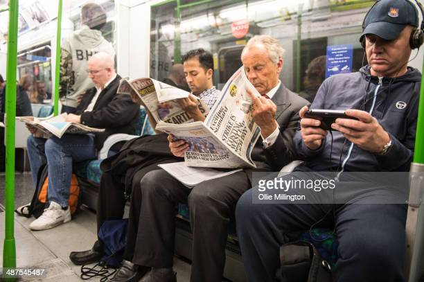 Commuters read newspaper coverage of the strikes on the underground on day two of a planned 48 hour underground train strike disrupting thousands of...