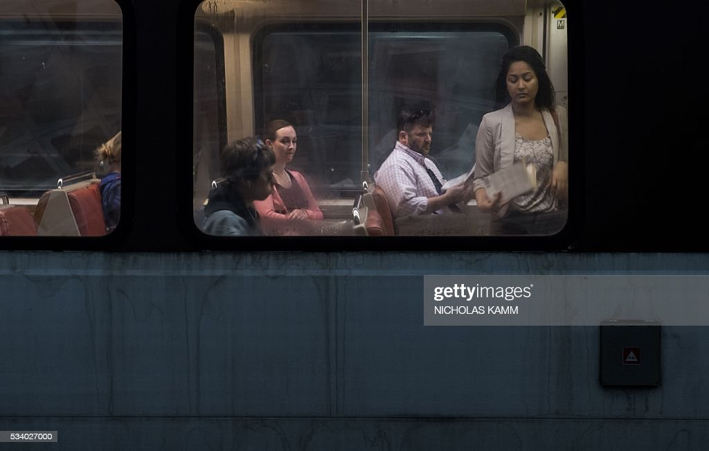 Commuters ride a Metro train at the L'Enfant Plaza station in Washington, DC, on May 24, 2016. Paul Wiedefeld, who used to run the Baltimore-Washington international airport, took over as Metrorail's new general manager in November 2015, assuming what was probably the least wanted job in the city at a really tense time. Wiedefeld has since presented a long-term maintenance plan to improve the system. / AFP / Nicholas Kamm