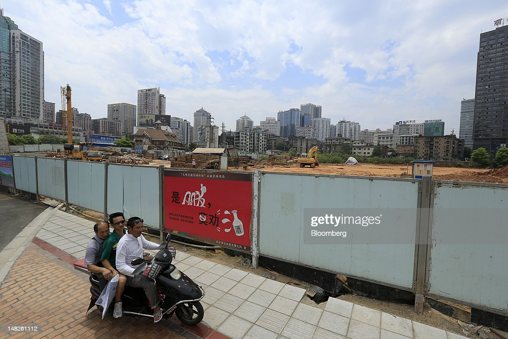 Commuters ride an electric scooter past a construction site in Changsha, Hunan Province, China, on Friday, July 13, 2012. Gross domestic product (GDP) expanded 7.6 percent in the second quarter of 2012 from a year earlier, China's National Bureau of Statistics said today in Beijing. Photographer: Nelson Ching/Bloomberg via Getty Images