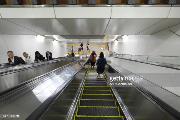 Commuters ride escalators at a subway station in Tokyo on September 15 2017 Millions of Japanese woke up in the early hours on September 15 as North...