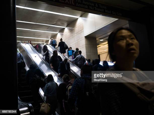 Commuters ride escalators at the Long Island Railroad Co concourse inside Pennsylvania Station in New York US on Friday May 26 2017 President Donald...