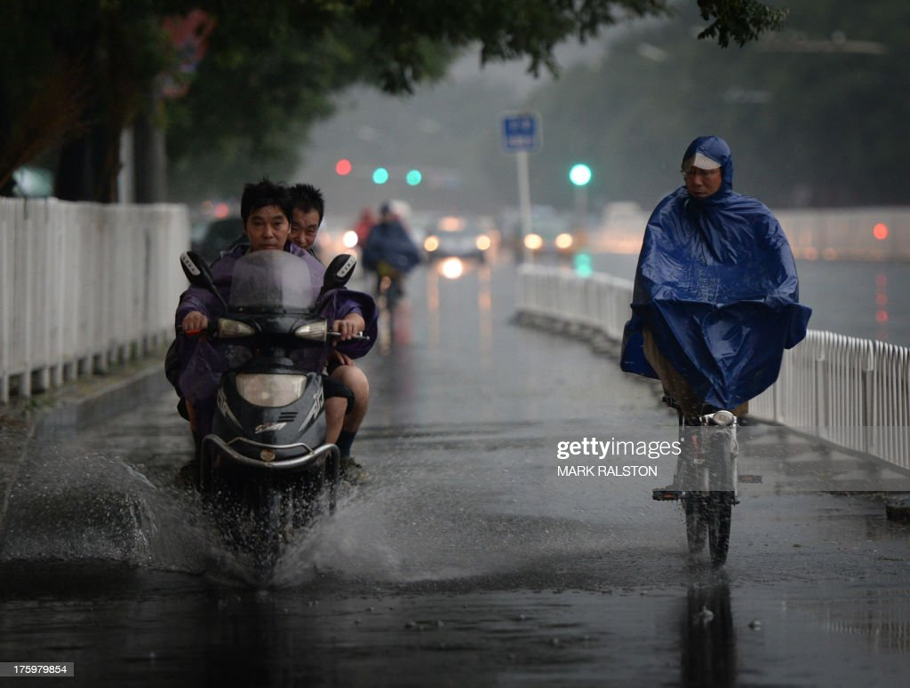 Commuters ride home on rain drenched streets as heavy thunderstorms continue to hit Beijing on August 11, 2013. A man was killed after being struck by lightning in the city and flights were delayed as China continues to experience extreme weather during the summer. AFP PHOTO/Mark RALSTON
