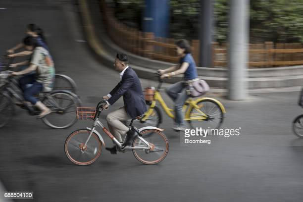 Commuters ride Mobike center left and Ofo Inc center right bicycles in Shanghai China on Thursday May 25 2017 In China abicyclesharingphenomenon is...