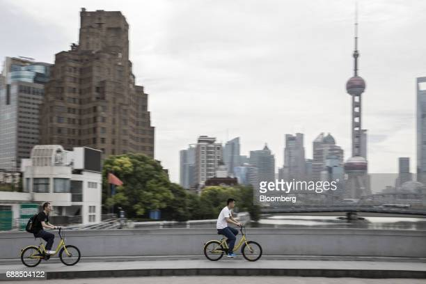 Commuters ride Ofo Inc bicycles along a sidewalk in Shanghai China on Thursday May 25 2017 In China abicyclesharingphenomenon is changing the way...
