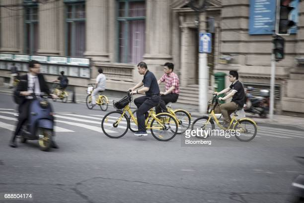 Commuters ride Ofo Inc bicycles along a sidewalk in Shanghai China on Thursday May 25 2017 In China a bicyclesharing phenomenon is changing the way...