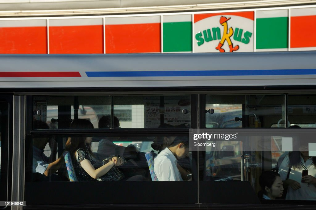 Commuters ride on a bus in front of a Sunkus convenience store, operated by Circle K Sunkus Co., in Yokohama City, Kanagawa Prefecture, Japan, on Tuesday, Sept. 11, 2012. Sales at Japan's convenience stores declined 3.3 percent in July from a year ago on a same-store basis, according to the Japan Franchise Association. Photographer: Akio Kon/Bloomberg via Getty Images
