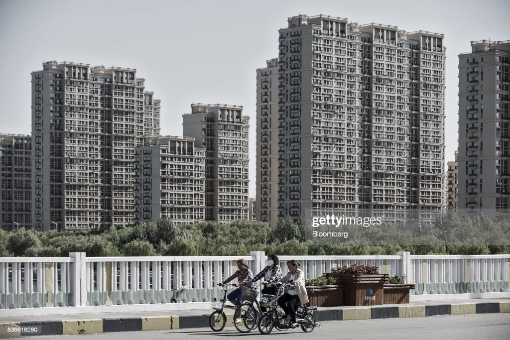 Commuters ride on bicycles past new residential buildings in Baotou, Inner Mongolia, China, on Friday, Aug. 11, 2017. China's economy showed further signs of entering a second-half slowdown, as curbs on property, excess borrowing and industrial overcapacity began to bite. Photographer: Qilai Shen/Bloomberg via Getty Images