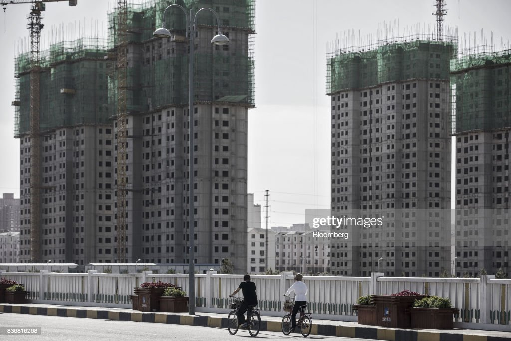 Commuters ride on bicycles past residential buildings under construction in Baotou, Inner Mongolia, China, on Friday, Aug. 11, 2017. China's economy showed further signs of entering a second-half slowdown, as curbs on property, excess borrowing and industrial overcapacity began to bite. Photographer: Qilai Shen/Bloomberg via Getty Images