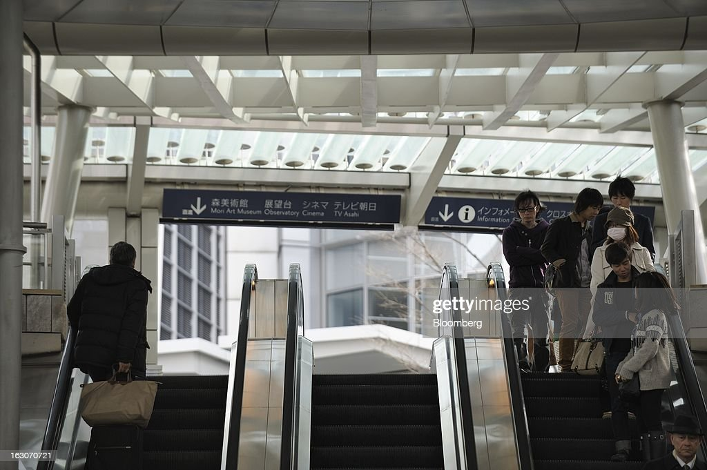 Commuters ride on escalators beneath the Roppongi Hills Mori Tower, operated by Mori Building Co., in Tokyo, Japan, on Friday, March 1, 2013. Mori Building Co., Japan's biggest closely held developer, said it plans to attract global companies to its new building set to open in 2014, its biggest project since Roppongi Hills opened a decade ago. Photographer: Akio Kon/Bloomberg via Getty Images