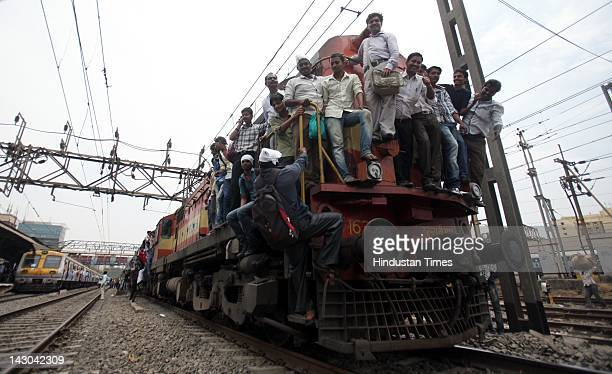 Commuters ride on the outside a local train in Vidyavihar as many people were stranded after a disruption on the on central line April 18 2012 in...