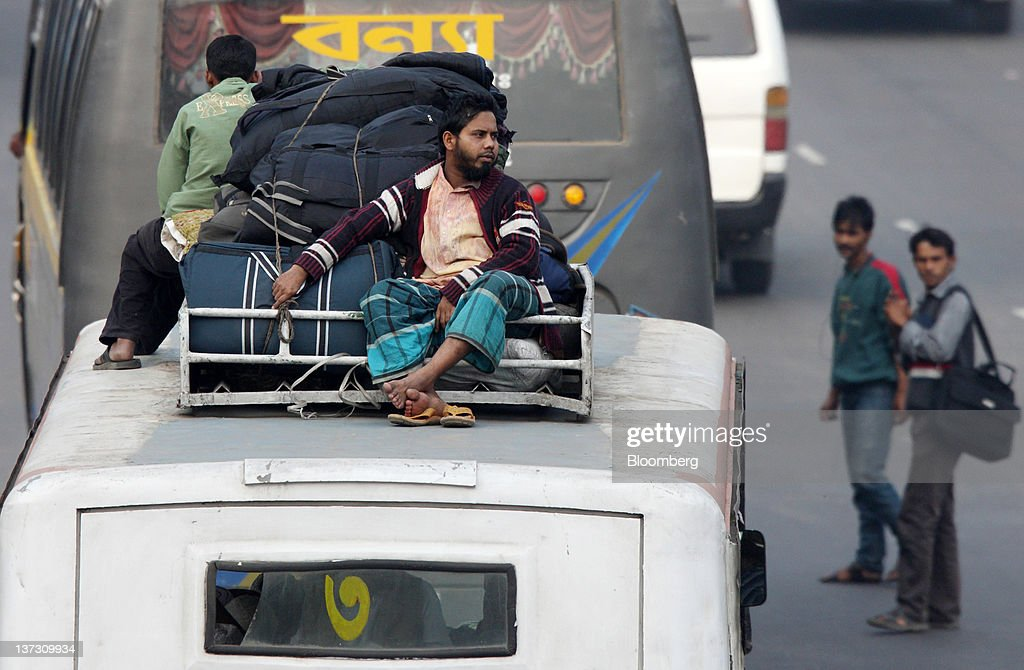 Commuters ride on the roof of a bus in Dhaka, Bangladesh, on Saturday, Jan. 7, 2012. Bangladesh's central bank this month raised interest rates for the second time in four months to curb inflation that has exceeded 9 percent since the start of 2011. Photographer: Tomohiro Ohsumi/Bloomberg via Getty Images