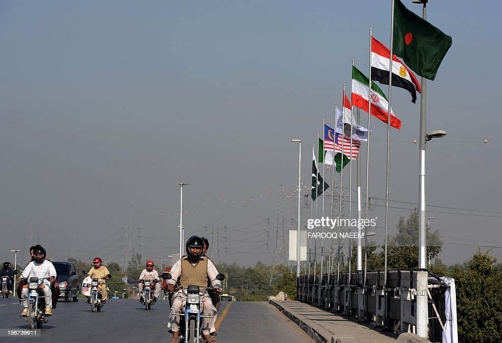 Commuters ride past flags of D-8 member nations ahead of the D8 summit in Islamabad on November 20, 2012. The biannual summit, established in 1997, will focus on economic challenges, development and peace in the region and among member countries. AFP PHOTO/Farooq NAEEM