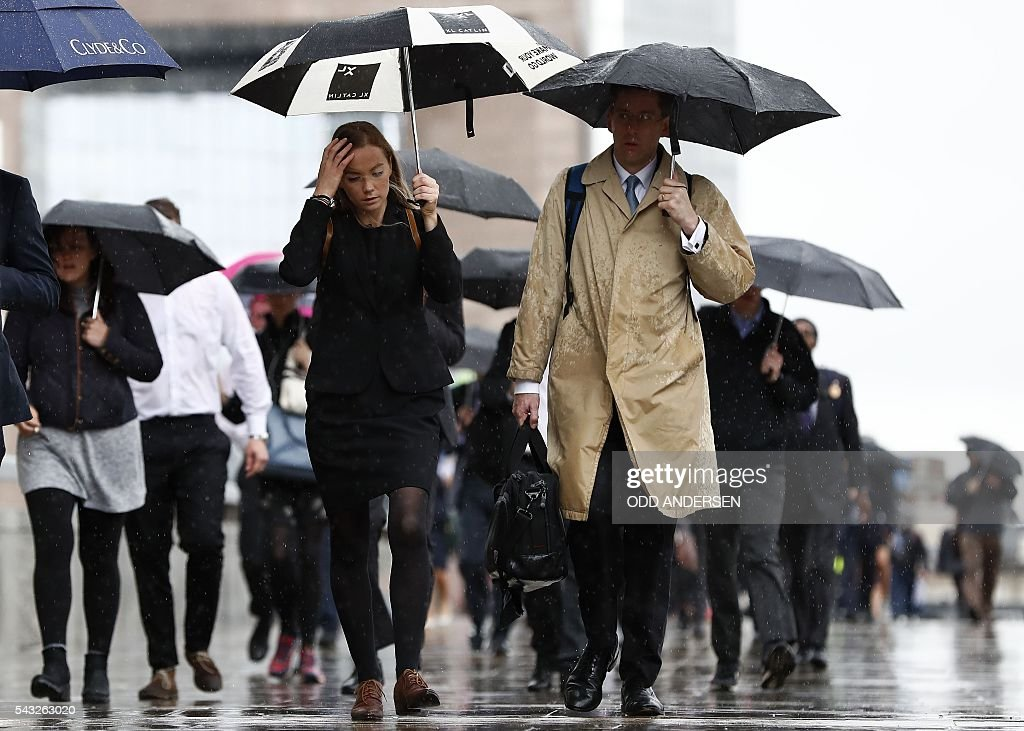 Commuters shelter from the rain beneath umbrellas as they head into the City of London across London Bridge in central London on June 27, 2016. Britain should only trigger Article 50 to leave the EU when it has a 'clear view' of how its future in the bloc looks, finance minister George Osborne said Monday following last week's shock referendum. / AFP / ODD