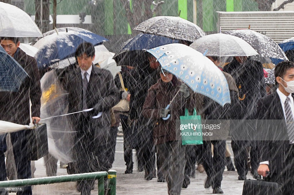Commuters shelter from the snow under umbrellas whilst on their way to work in Tokyo on February 6, 2013. The Japan Meteorological Agency was forecasting heavy snow on Pacific coastal regions in western and eastern Japan on February 5 and February 6 as a developing low pressure system passed along the south of the Japanese archipelago.