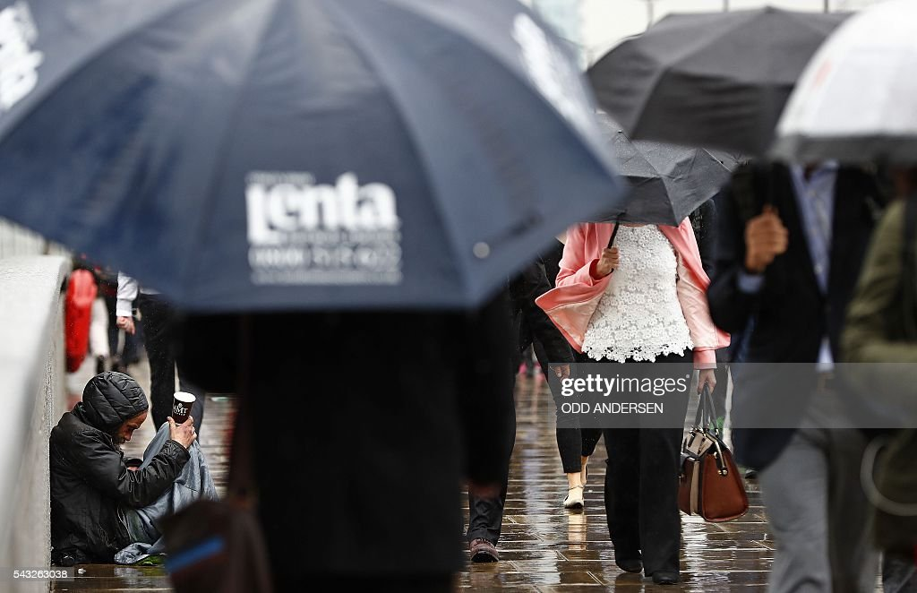Commuters sheltering from the rain beneath umbrellas pass a person asking for money as they head into the City of London across London Bridge in central London on June 27, 2016. Britain should only trigger Article 50 to leave the EU when it has a 'clear view' of how its future in the bloc looks, finance minister George Osborne said Monday following last week's shock referendum. / AFP / ODD