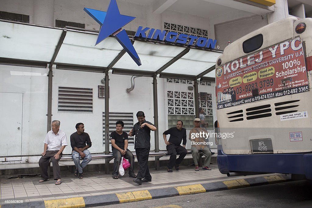 Commuters sit at a bus stop in Kuala Lumpur, Malaysia, on Tuesday, July 22, 2014. Malaysian Airline System Bhd. (MAS), reeling from its second disaster in four months, plans to present a revival plan to its state-run parent Khazanah Nasional Bhd. this week, people familiar with the matter said, amid reports the national carrier is likely near the end of its days as a publicly traded company. Photographer: Brent Lewin/Bloomberg via Getty Images