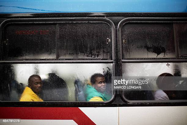 Commuters sit inside a bus that will take them home outside the stadium at the end of the memorial service for late South African President Nelson...