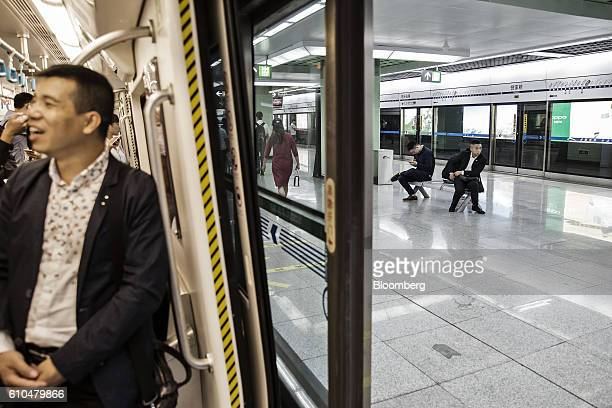Commuters sit on a platform bench as the doors of a train open at a subway station in Chengdu China on Monday Sept 19 2016 China faces unprecedented...