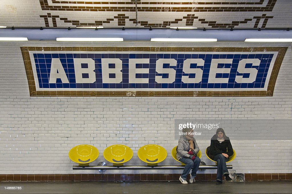 Commuters sitting on platform seats at Abbesses Metro station.