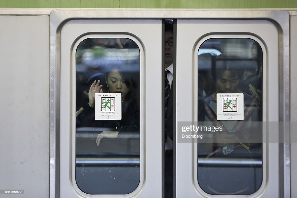 Commuters stand aboard a train as the doors close in Tokyo, Japan, on Thursday, Oct. 17, 2013. Asian stocks rose, sending the benchmark index to a five-month high, while the regions bond risk fell and emerging-market currencies strengthened after U.S. lawmakers voted to raise the nations debt limit. Photographer: Kiyoshi Ota/Bloomberg via Getty Images