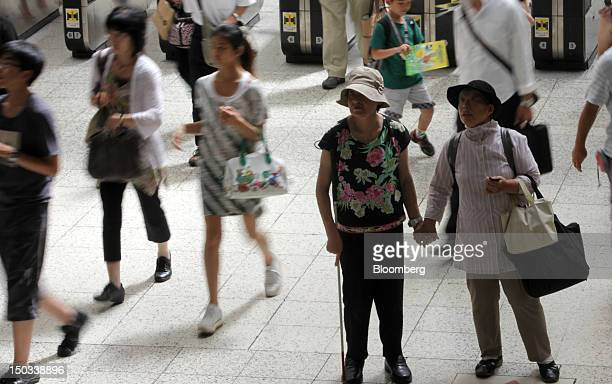 Commuters stand at a station in Tokyo Japan on Thursday Aug 16 2012 With 7 million baby boomers starting to retire this year and about onethird of...