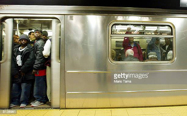 Commuters stand in a subway car as the doors close in Grand Central Station March 24 2004 in New York City The New York subway system is celebrating...