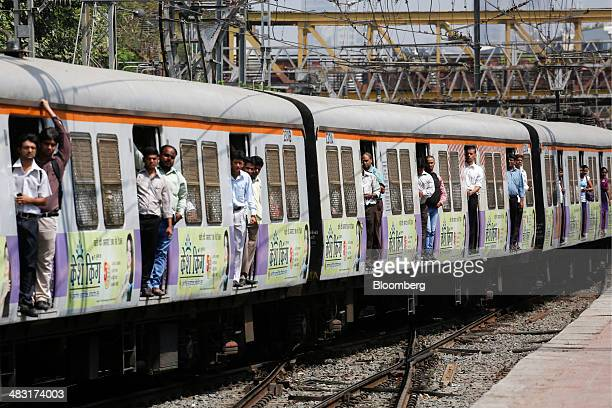 Commuters stand in doorways while they wait to disembark from a train as it arrives at Churchgate Station near the financial district of Mumbai India...