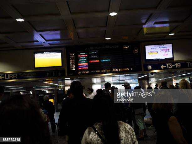 Commuters stand in front of a departure board at the Long Island Railroad Co concourse inside Pennsylvania Station in New York US on Friday May 26...