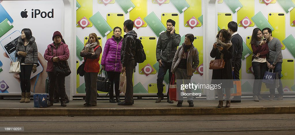 Commuters stand in front of an advertisement for Apple Inc. iPods at a tram stop in Hong Kong, China, on Friday, Jan. 4, 2013. Chief Executive Leung Chun-ying, who has been buffeted by student protests and low popularity since taking office on July 1, has pledged to tackle Asia's biggest wealth gap as the division between poor and rich widened to its worst level since at least 1971. Photographer: Jerome Favre/Bloomberg via Getty Images