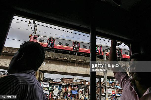 Commuters stand in the doorway of a train as another passes by on an elevated track in Mumbai India on Friday July 4 2014 Indian Railways' annual...