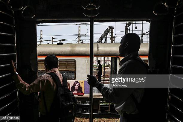 Commuters stand in the doorway of a train as it approaches Chhatrapati Shivaji Terminus railway station in Mumbai India on Friday July 4 2014 Indian...