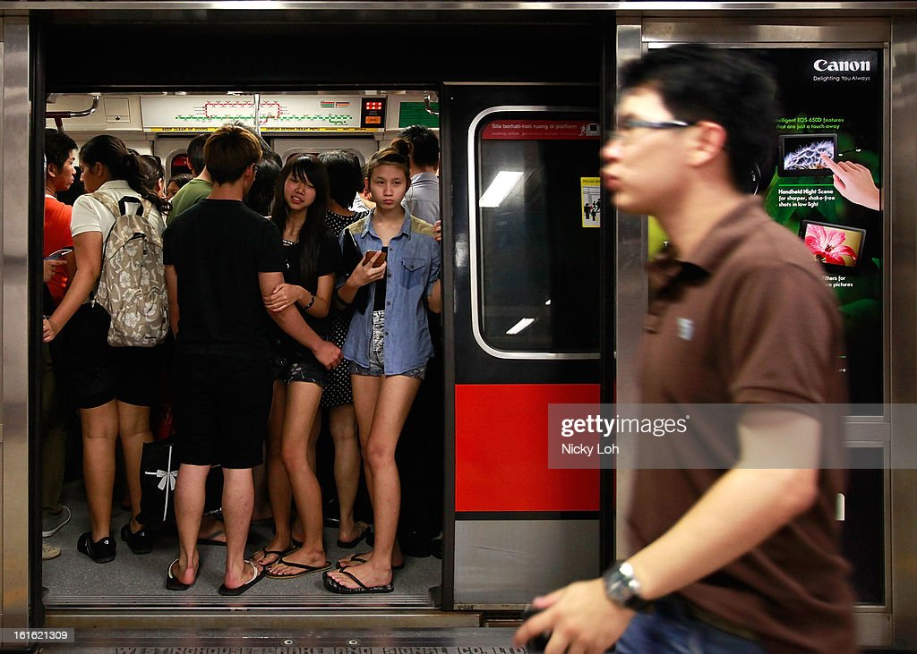 Commuters stand inside a train in the Tanjong Pagar MRT station during rush hour at the central business district area on February 13, 2013 in Singapore. The government white paper revealed Singapore's population may increase 30% to over 6.9 million by 2030, with nearly half the population expected to be foreign-born. Many local residents are critising the plan concerned about the added strain on housing, transportation and healthcare and the diminishing identity of the Singaporean community.