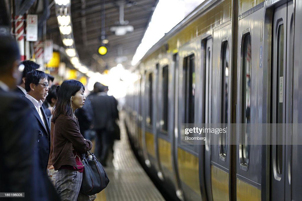 Commuters stand on a platform as they wait to board a train at a station in Tokyo, Japan, on Thursday, Oct. 17, 2013. Asian stocks rose, sending the benchmark index to a five-month high, while the regions bond risk fell and emerging-market currencies strengthened after U.S. lawmakers voted to raise the nations debt limit. Photographer: Kiyoshi Ota/Bloomberg via Getty Images