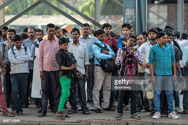 Commuters stand on a platform at Kurla railway station in Mumbai India on Wednesday April 15 2015 India's economic growth will power past China's for...