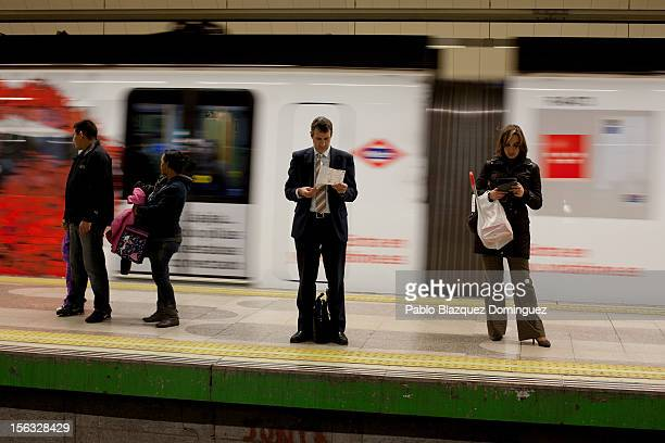 Commuters stand on an underground train's platform on November 13 2012 in Madrid Spain Spain's trade unions have called a general strike for November...
