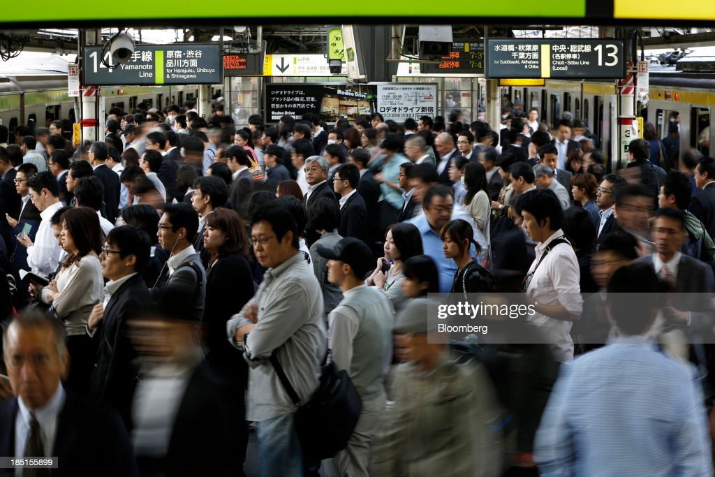 Commuters stand on the platform of a train station in Tokyo, Japan, on Thursday, Oct. 17, 2013. Asian stocks rose, sending the benchmark index to a five-month high, while the regions bond risk fell and emerging-market currencies strengthened after U.S. lawmakers voted to raise the nations debt limit. Photographer: Kiyoshi Ota/Bloomberg via Getty Images