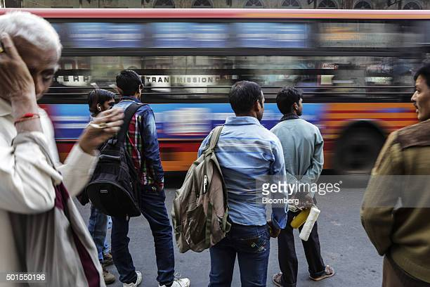 Commuters stand waiting for a bus in the Kalupur Road area of Ahmadabad Gujarat India on Monday Dec 14 2015 India's rupee is feeling the heat as the...