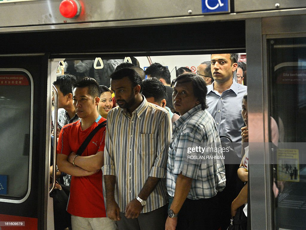 Commuters stands at the doorway in a crowded train at the subway station in Singapore on February 13, 2013. Singapore on February 4 defended its population policies after an outcry over a forecast that it could have 30 percent more people in less than 20 years, with foreigners forming almost half the total.