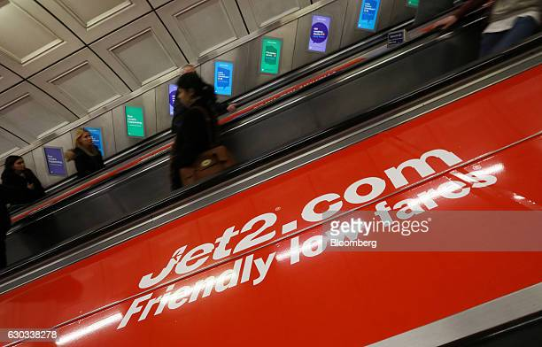 Commuters travel on escalators past posters advertising Jet2com holidays at Liverpool Street railway and underground station in London UK on...