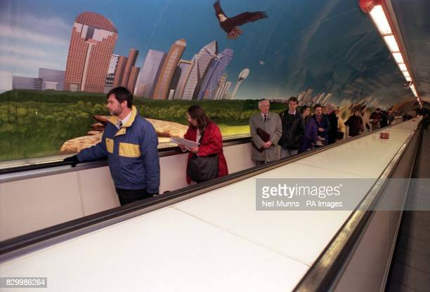 Commuters travel past London's largest landscape painting along the wall of the Travolator at Bank Underground Station in London after it was...