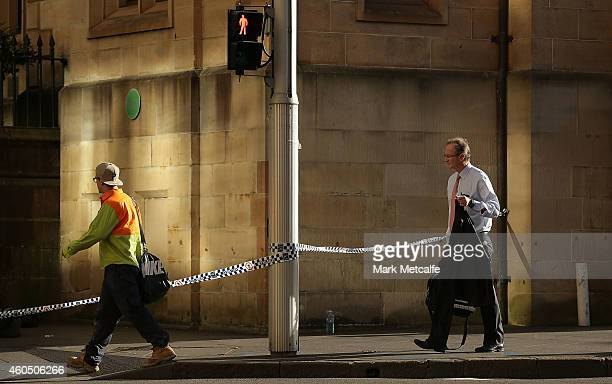 Commuters travel past police tape on St James Rd on their way to work on December 16 2014 in Sydney Australia The siege in Sydney's Lindt Cafe in...