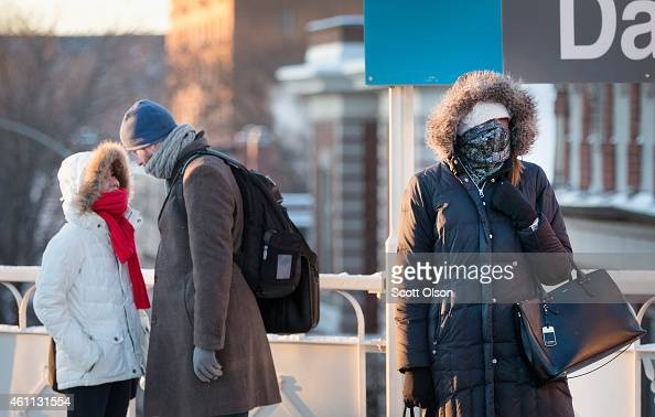 Commuters try to stay warm as they wait for a train on an L platform during the early morning rush while temperatures hovered around zero degrees...