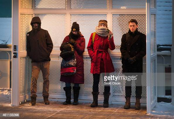 Commuters try to stay warm as they wait for a train on an L platform during morning rush while temperatures hovered around zero degrees Fahrenheit on...