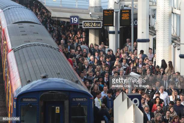 Commuters using overground train services wait to pass through the barriers at Waterloo station London on the second day of a 48 hour strike by tube...