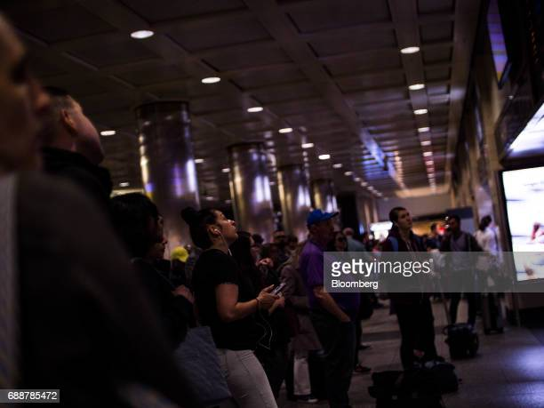Commuters view a departure board at the Long Island Railroad Co concourse inside Pennsylvania Station in New York US on Friday May 26 2017...