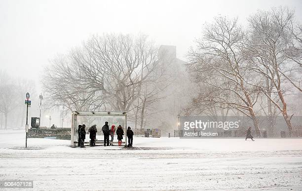 Commuters wait at a bus station on West 81 Street during heavy snow fall and strong wind gusts on January 23 2016 in New York City A major Nor'easter...