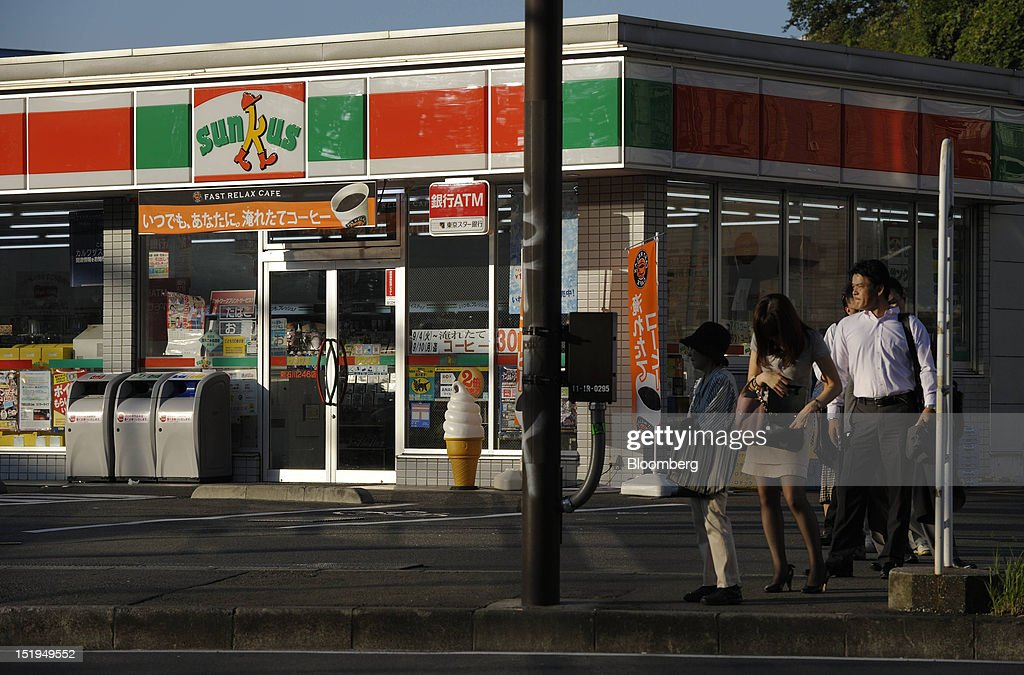 Commuters wait at a bus stop in front of a Sunkus convenience store, operated by Circle K Sunkus Co., in Yokohama City, Kanagawa Prefecture, Japan, on Tuesday, Sept. 11, 2012. Sales at Japan's convenience stores declined 3.3 percent in July from a year ago on a same-store basis, according to the Japan Franchise Association. Photographer: Akio Kon/Bloomberg via Getty Images