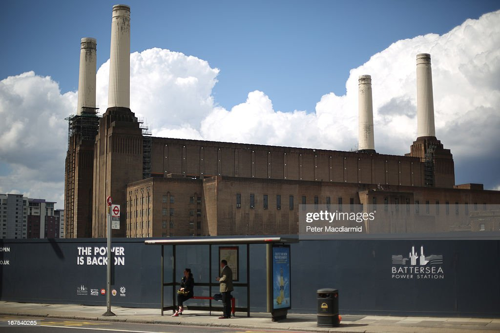 Commuters wait at a bus stop in front of Battersea power station on April 26, 2013 in London, England. Built in the 1930s, with an identical second section added in the 1950s, the Grade II* listed building last generated electricity in 1983. The 15.7 hectare site on the south bank of The River Thames is being re-developed. Over the next 11 years 3400 homes, office space and a theatre will be built in and around the power station which is still the largest brick building in Europe.